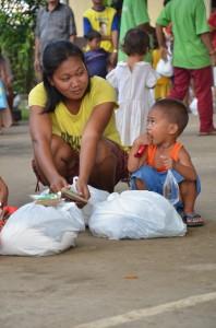 救援物資の受け取りには子供たちも親の手伝いで、列に並び、家まで物資を運んだ