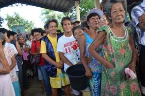 救援物資配布の列に並ぶ村の高齢者たち