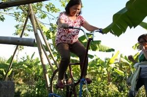自転車型ポンプを動かすヒルダさん