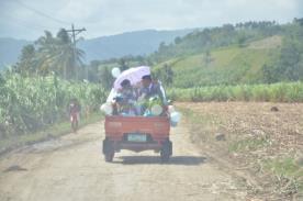軽トラックの荷台に乗って教会へ向かう2人
