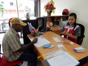 カカオキタ貯蓄プログラム担当のヨセフ(左)が民衆信託銀行で入金手続き