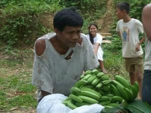 生産者は重いバナナを担いで山道をもくもくと歩きます。