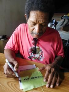 カカオ袋のラベルを書く、カカオキタ社代表のデッキーさん