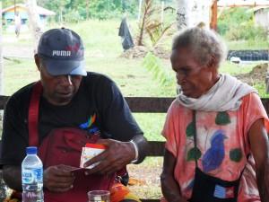 「わたしの貯金、いくらになった?」(カカオキタスタッフのヨセフさん/左、ブラップ村のルス・マンゴさん/右)